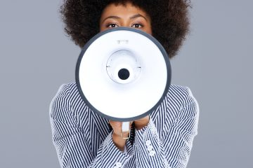 African American woman speaking into a megaphone making a public